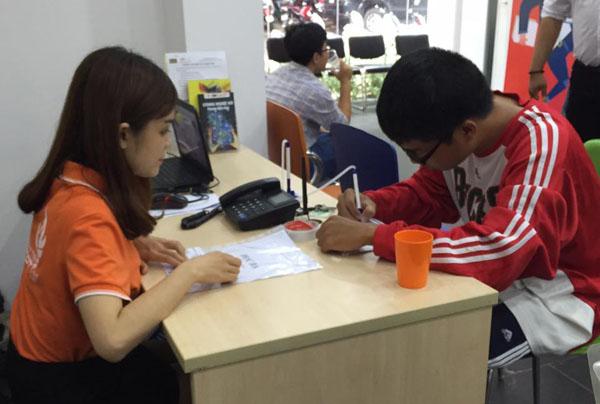 Chuyên viên tư vấn đang hướng dẫn các thí sinh làm thủ tục nhập học