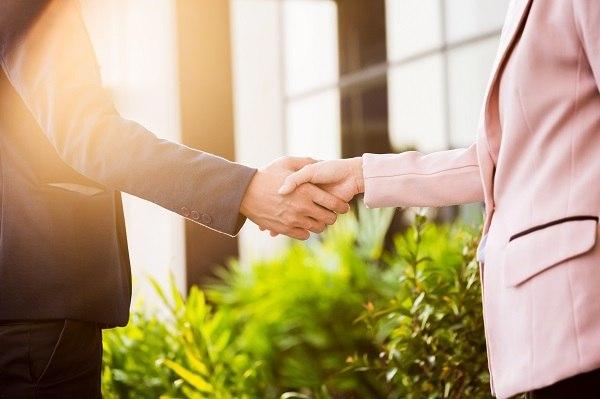 Closeup friendly meeting handshake between business woman and b